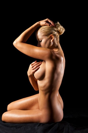 Stock Photo: 4288-1418 Nude blonde Caucasian woman sitting with face and breast obscured on a black background.