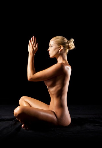 Stock Photo: 4288-1419 Nude blonde Caucasian woman sitting cross-legged with palms pressed together on a black background.