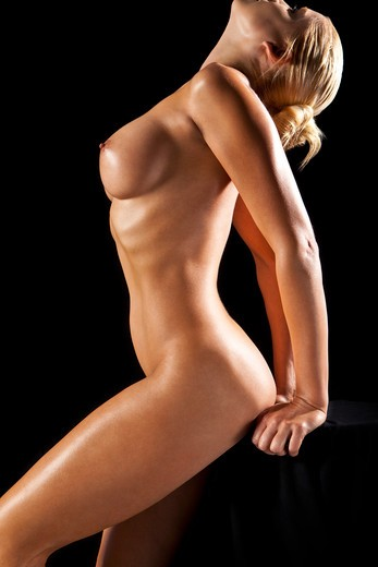 Nude blonde Caucasian woman with arched back leaning on a black background. : Stock Photo