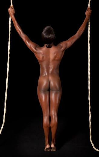 Nude African-American woman standing between two ropes on a black background. : Stock Photo