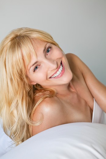 Stock Photo: 4288-1434 Smiling blonde Caucasian woman lying on a white bed.