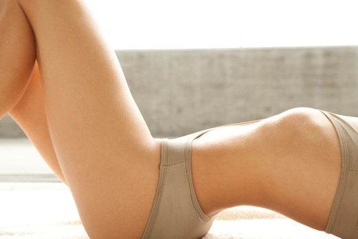 Stock Photo: 4288-1439 Arched torso and upper legs of a Caucasian woman in taupe bra and panties.