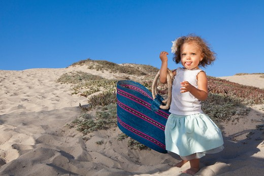 Stock Photo: 4288-1456 Little girl with beach tote sticks out tongue.