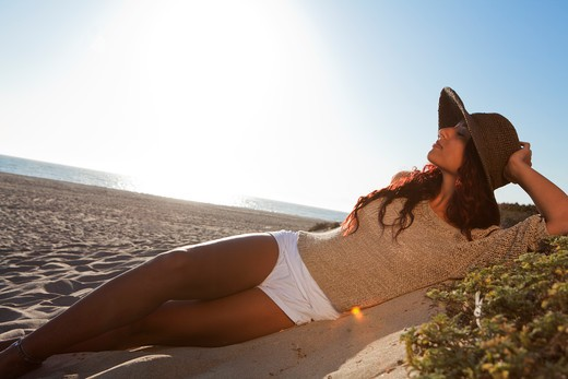 Stock Photo: 4288-1461 Young woman in brown straw hat lounging on beach.
