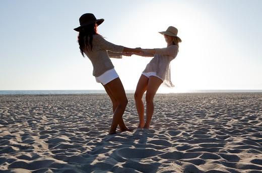Stock Photo: 4288-1463 Two women swing around on sandy beach.