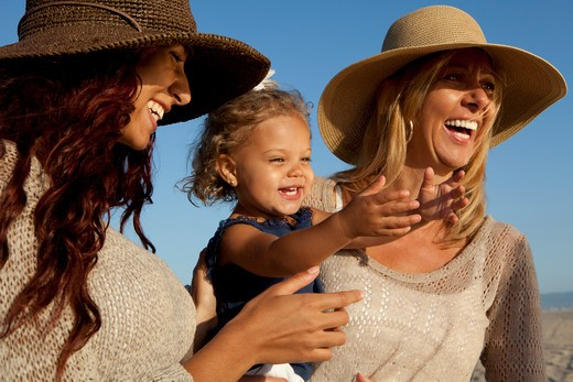 Stock Photo: 4288-1464 Two smiling women in straw hats with little girl.