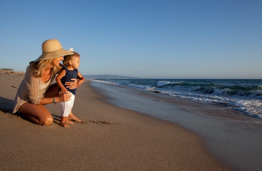 Blonde woman holds little girl on sandy beach. : Stock Photo