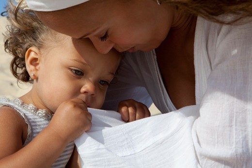Stock Photo: 4288-1473 Woman in white shirt holds tired little girl.
