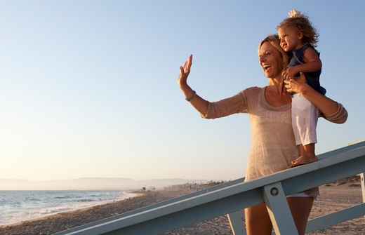 Stock Photo: 4288-1474 Waving woman supports little girl on incline.
