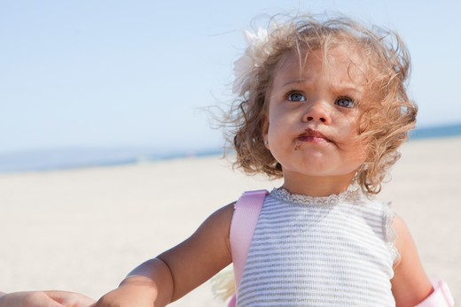 Little girl with striped shirt and chocolate on face at beach. : Stock Photo