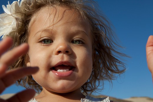 Little girl with blue eyes and white flower in hair. : Stock Photo