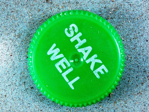 Green bottle cap printed with Shake Well. : Stock Photo