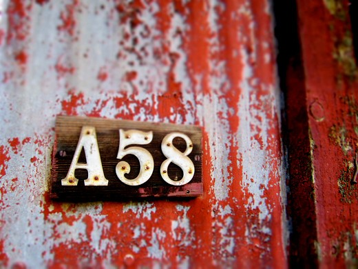 Stock Photo: 4288-1519 Wooden sign for A58 on corrugated metal with weathered red paint.