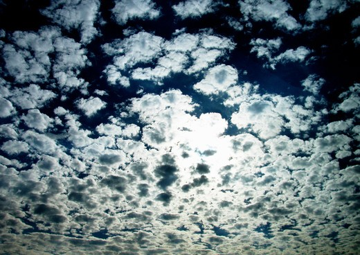 White clouds backlit by the sun in a blue sky. : Stock Photo