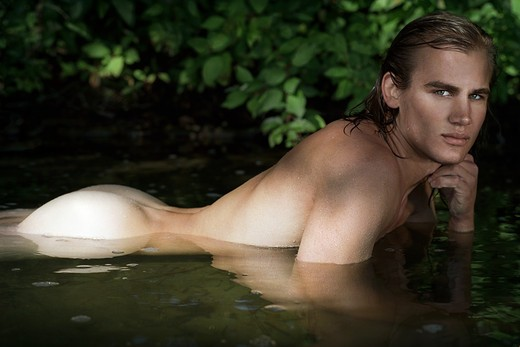 Nude, partially submerged man with green eyes. : Stock Photo