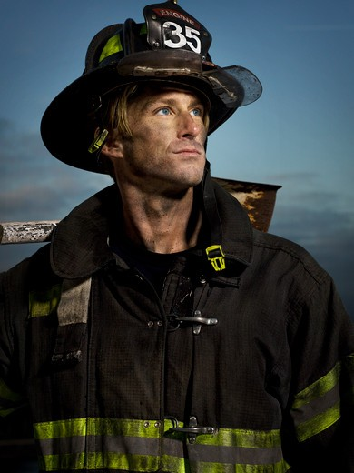 Stock Photo: 4288-1603 Dirty firefighter with blue eyes looking to side.