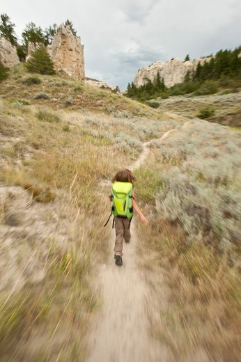 Stock Photo: 4288-1640 Girl with backpack running on trail, Montana, USA.