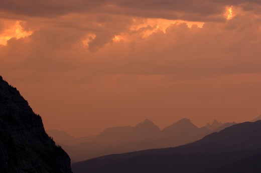 Mountains silhouetted by setting sun, Glacier National Park, USA. : Stock Photo