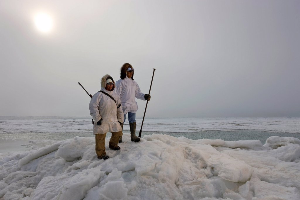 Stock Photo: 4289-10145 Male and female Inupiaq Eskimo hunters wearing their Eskimo parka´s Atigi carry a rifle and walking stick while looking out over the Chukchi Sea, Barrow, Arctic Alaska, Summer