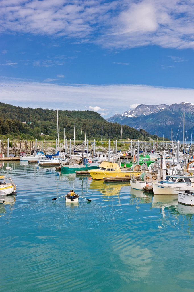 Children rowing a small dingy in tthe Haines Small Boat Harbour next to Commercial fishing boats, Coast Mountains in the background, Haines, Southeast Alaska, Summer : Stock Photo