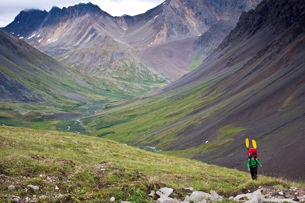 Stock Photo: 4289-11986 Woman with a packraft hiking upper Windy Creek to a mountain pass under cloudy skies, Denali National Park & Preserve, Alaska Range, Interior Alaska, Summer