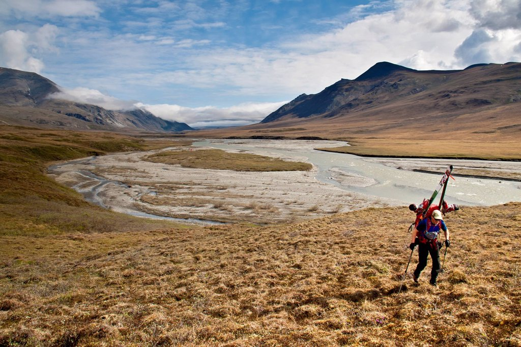 Backpacker carrying skis above the Hulahula River on the approach to Mount Chamberlin, Brooks Range, Arctic National Wildlife Refuge, Summer in Arctic Alaska : Stock Photo