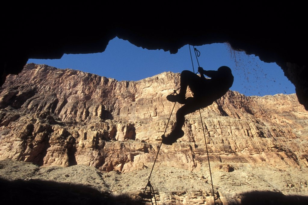 Stock Photo: 4289-12342 Woman rope climber silhouetted under ledge Grand Canyon National Park Arizona USA