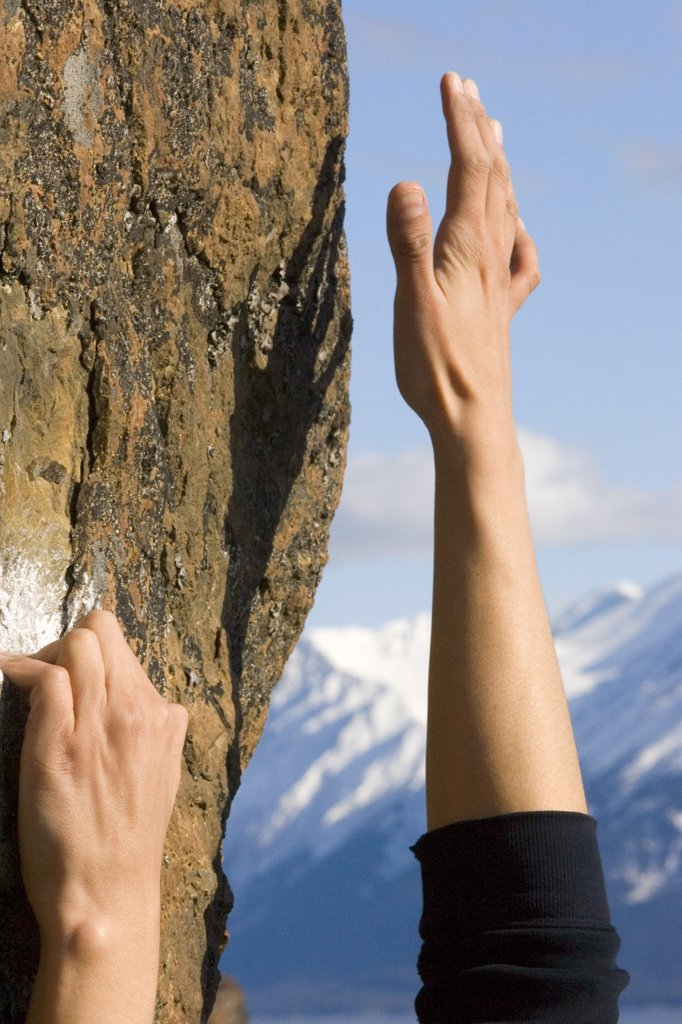 Hands of rock climber reaching for higher handhold Alaska Summer : Stock Photo
