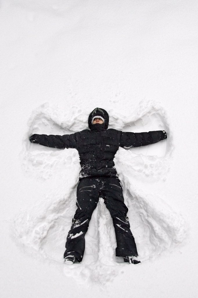 Girl laying in deep snow making a snow angel USA Winter : Stock Photo
