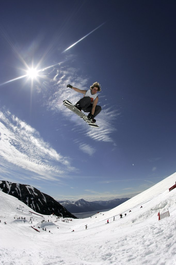 Snowboarder in doing mid_air stunt on mountain side wide angle view Alaska USA : Stock Photo