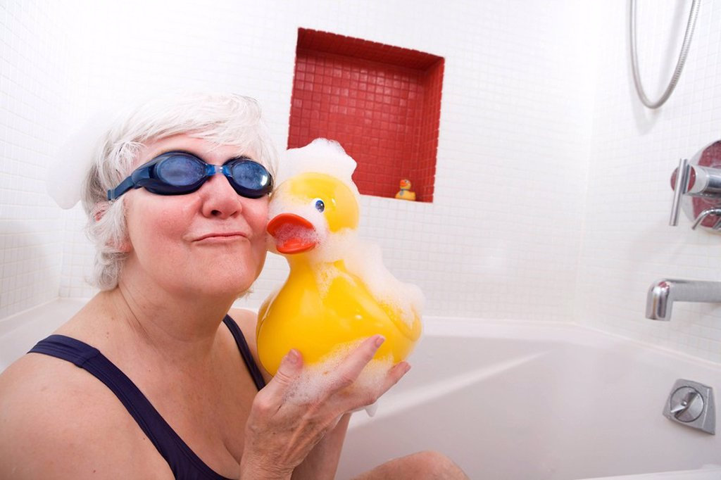Stock Photo: 4289-13265 Senior woman having some fun in the tub with a yellow rubber duck wearing swim goggles