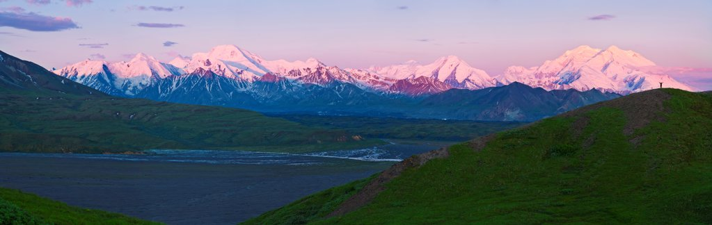 Panoramic view of hiker on Grassy Pass watching the sunrise on Thorofare River and Mt. McKinley, Denali National Park & Preserve, Interior Alaska, Summer : Stock Photo