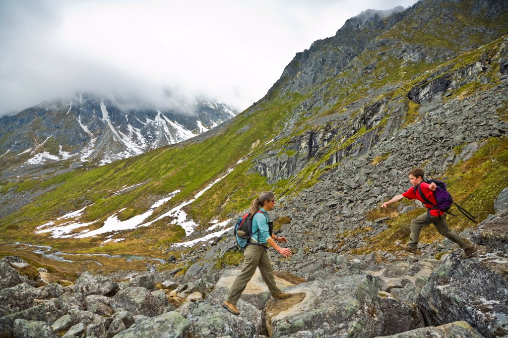 Stock Photo: 4289-13371 Young boy and mother boulder hopping along Reed Lakes Trail, Talkeetna Mountains, Southcentral Alaska, Spring