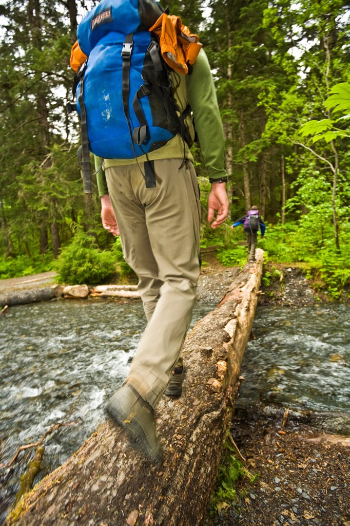 Stock Photo: 4289-13378 Male hiker crossing a log over Winner Creek, Chugach National Forest, Southcentral Alaska, Summer
