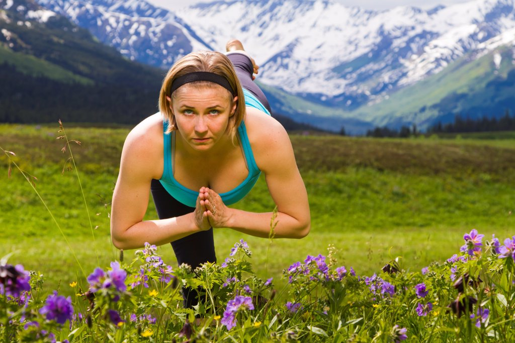 Stock Photo: 4289-13396 Woman practicing yoga in a mountain meadow of wild geraniums, Turnagain Pass, Chugach National Forest, Southcentral Alaska, Summer