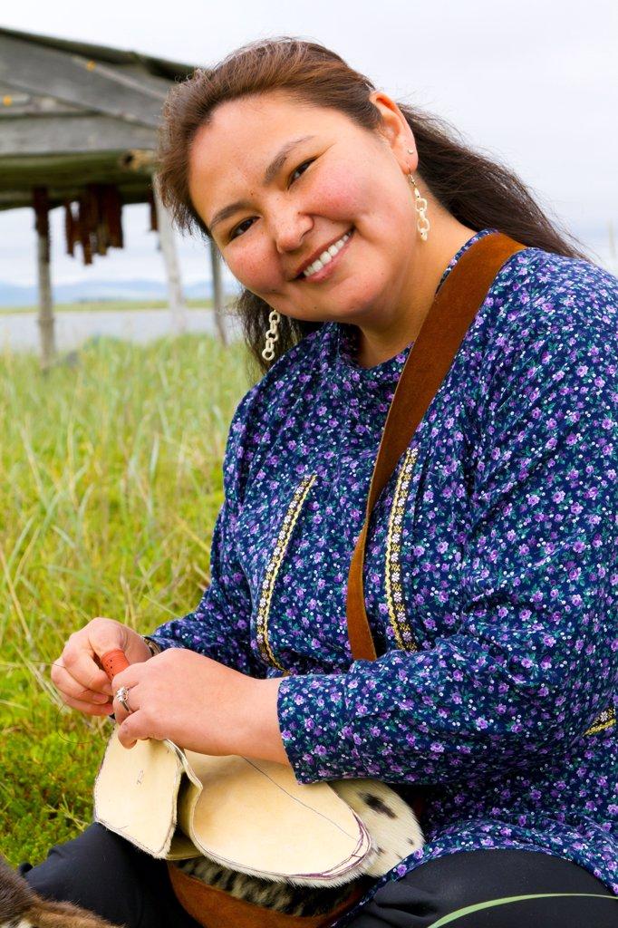 Stock Photo: 4289-13405 Inupiat woman wearing decorative kuspuk and sewing seal skin boots at fish camp near Safety Sound, Nome, Arctic Alaska, Summer