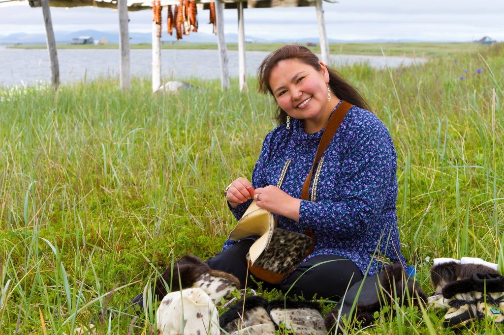 Inupiat woman wearing decorative kuspuk and sewing seal skin boots at fish camp near Safety Sound, Nome, Arctic Alaska, Summer : Stock Photo