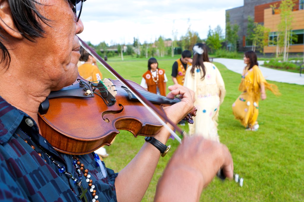Athabascan dancers & violinist perform in the lawn at the Morris_Thompson Cultural Center, Fairbanks, Interior Alaska, Summer : Stock Photo