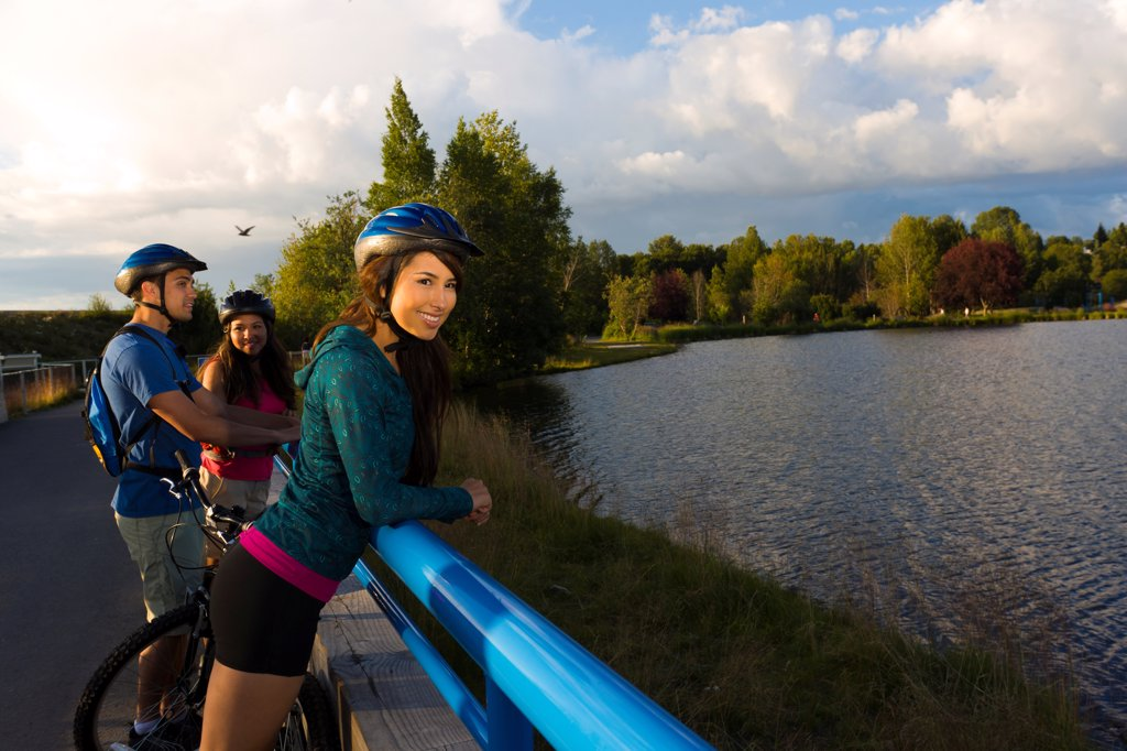Young adult bicyclists enjoy the view along the Tony Knowles Coastal Trail, Anchorage, Southcentral Alaska, Summer : Stock Photo
