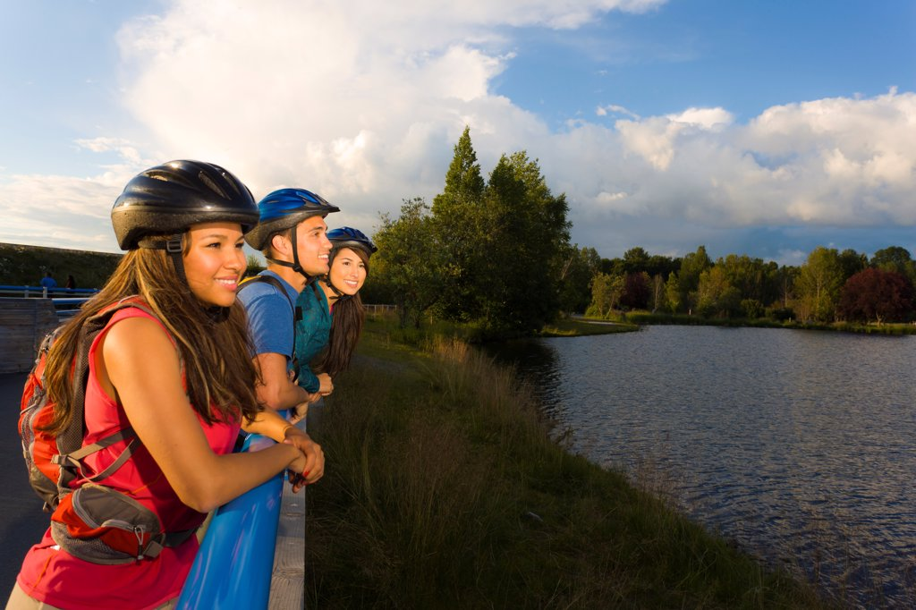 Stock Photo: 4289-13538 Young adult bicyclists enjoy the view along the Tony Knowles Coastal Trail, Anchorage, Southcentral Alaska, Summer