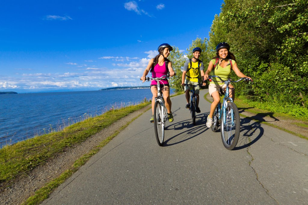 Group of young adults riding on the Tony Knowles Coastal Trail along Cook Inlet, Anchorage, Southcentral Alaska, Summer : Stock Photo
