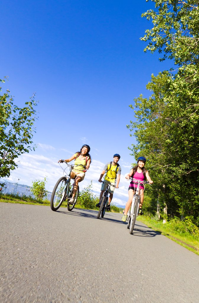 Stock Photo: 4289-13545 Group of young adults riding on the Tony Knowles Coastal Trail along Cook Inlet, Anchorage, Southcentral Alaska, Summer