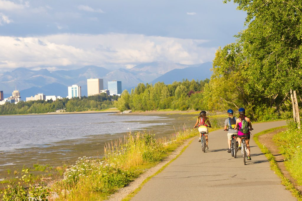 Stock Photo: 4289-13546 Group of young adults riding on the Tony Knowles Coastal Trail along Cook Inlet, Anchorage, Southcentral Alaska, Summer