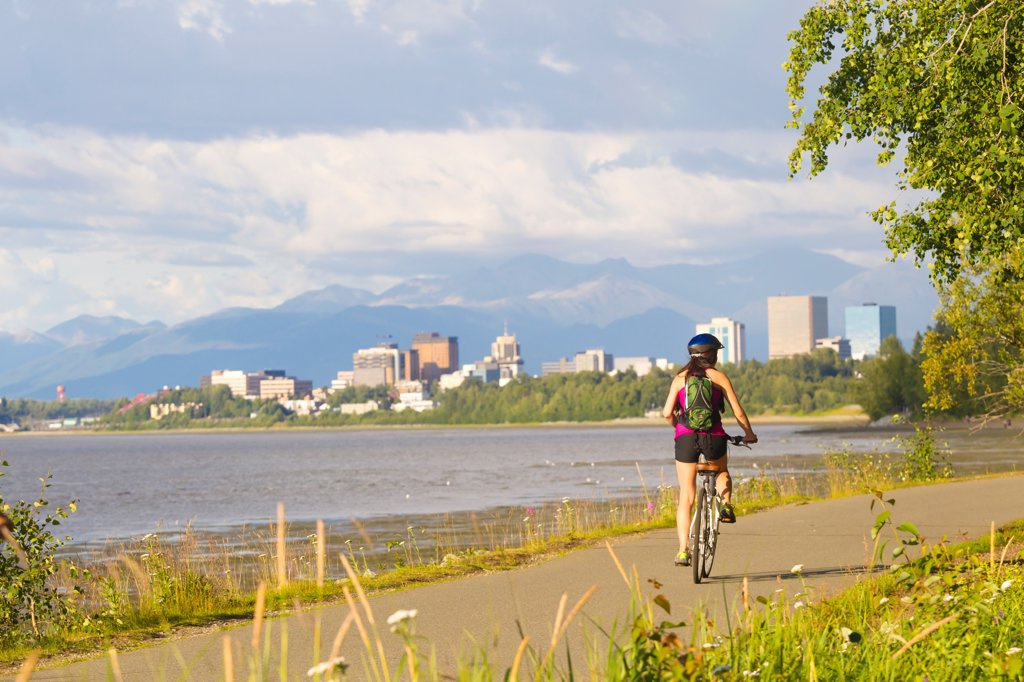 Young adult female riding on the Tony Knowles Coastal Trail along Cook Inlet, Anchorage, Southcentral Alaska, Summer : Stock Photo