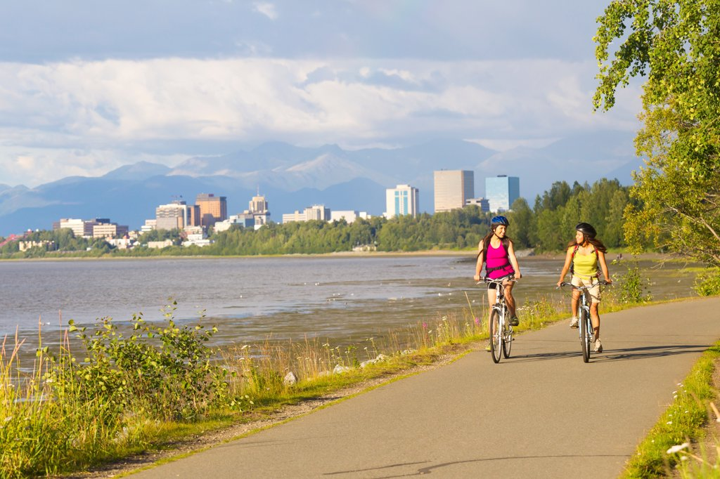 Young adult females riding on the Tony Knowles Coastal Trail along Cook Inlet, Anchorage, Southcentral Alaska, Summer : Stock Photo