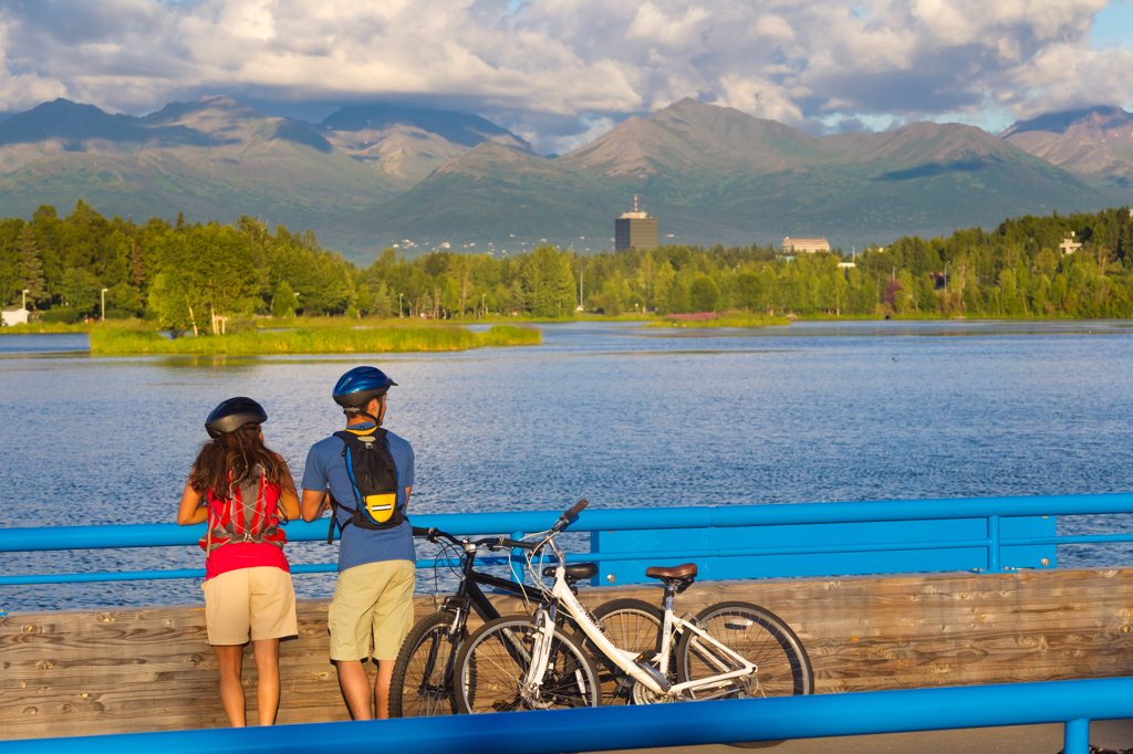 Stock Photo: 4289-13554 Young adult bicyclists stopped along the Tony Knowles Coastal Trail along Cook Inlet, Anchorage, Southcentral Alaska, Summer