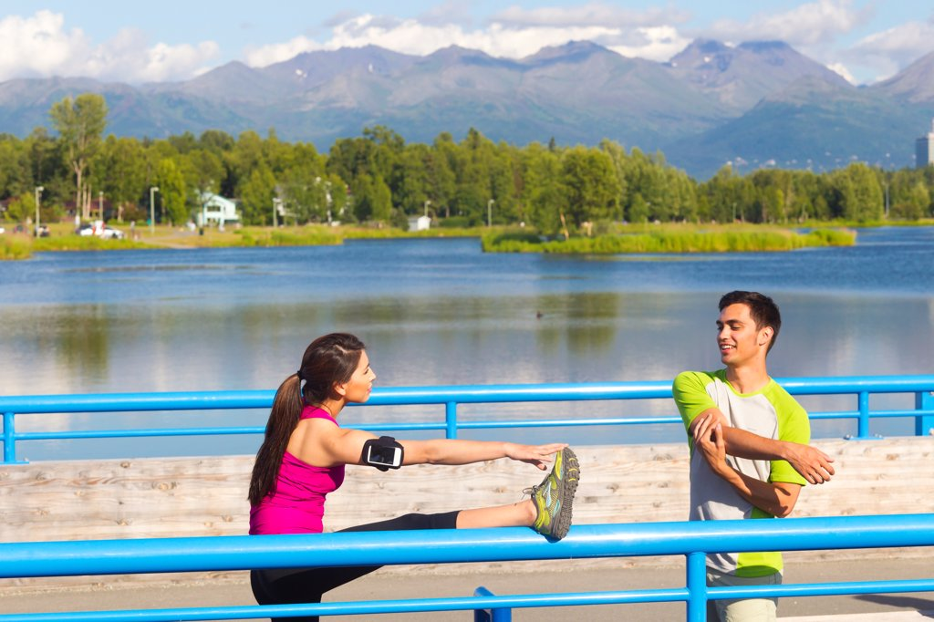 Stock Photo: 4289-13560 Young couple stretching on the Tony Knowles Coastal Trail near Westchester Lagoon, Anchorage, Southcentral Alaska, Summer