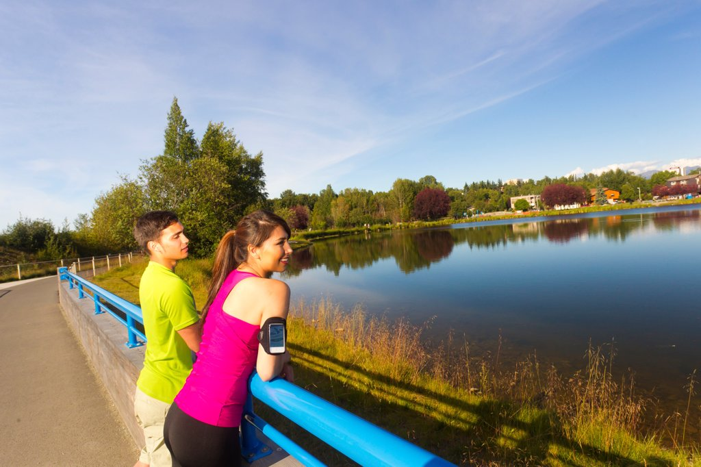 Stock Photo: 4289-13563 Young athletic couple enjoying the view on the Tony Knowles Coastal Trail near Westchester Lagoon, Anchorage, Southcentral Alaska, Summer