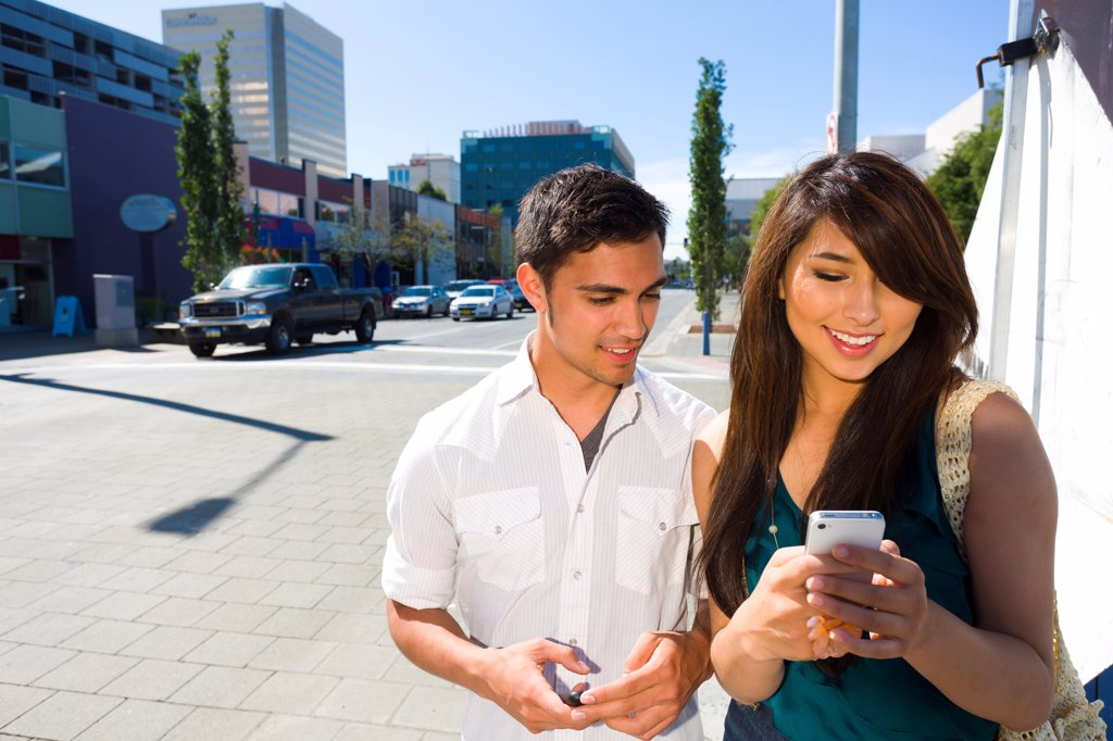 Stock Photo: 4289-13577 Young adult couple looking at smart phones in downtown street, Anchorage, Southcentral Alaska, Summer
