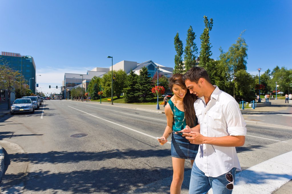 Stock Photo: 4289-13578 Young adult couple looking at smart phones as they cross a downtown street, Anchorage, Southcentral Alaska, Summer